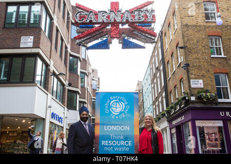 """London, UK. 18th March, 2019. Ranjit Baxi, Founding President of the Global Recycling Foundation, and Susie Burrage, President of British Metals Recycling Association, mark the celebration of the second annual Global Recycling Day beneath the Carnaby Street sign. This year's theme is """"Recycling into the Future"""", focusing on the importance and power of youth, innovation and education in ensuring a brighter future for the planet. Credit: Mark Kerrison/Alamy Live News - Stock Image"""