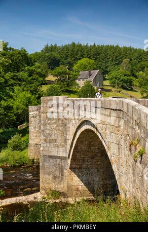 UK, Yorkshire, Wharfedale, walker crossing Barden Bridge, River Wharfe in mid summer - Stock Image