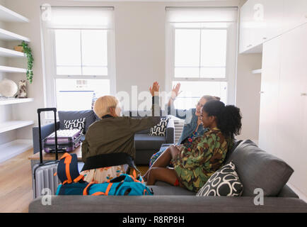 Young women friends with suitcases high-fiving in living room - Stock Image
