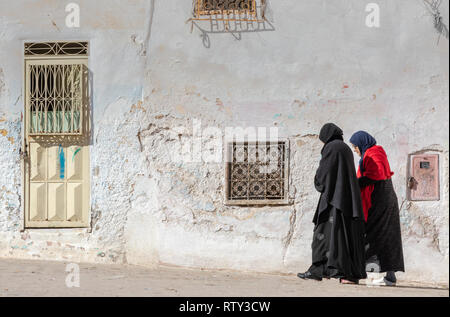 Two muslim woment walking in the ruins of the ancient Jewish Quarter (mellah) in Sefrou, Morocco - Stock Image