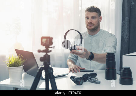 technology blogger recording headphone review in front of camera at home - Stock Image