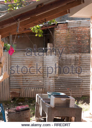 Zinc fence and concrete sink in a backyard in Jinotega, Nicaragua - Stock Image