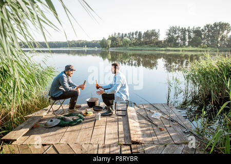 Landscape view on the lake with two male friends sitting together with beer during the fishing process - Stock Image