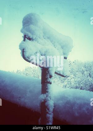 Snow covered road sign - Stock Image