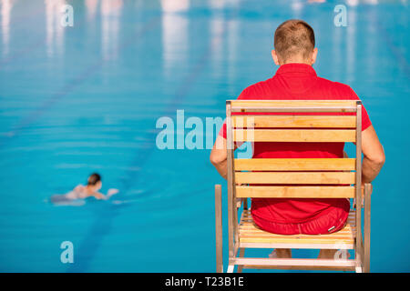 Lifeguard on duty, sitting in lifeguard chair, overlooking pool. Polarizing filter. - Stock Image