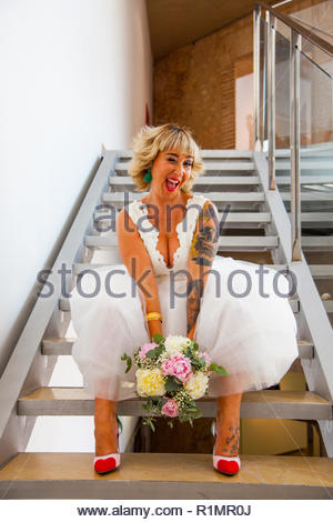 Beautiful bride sitting on a ladder with her bouquet with a funny gesture - Stock Image