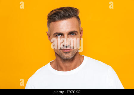 Image of sexual man 30s in white t-shirt posing at camera with confident look isolated over yellow background - Stock Image
