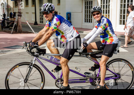 Miami Beach Florida Ocean Drive New Year's Day man woman couple cyclists tandem helmets exercise health fitness synchronize fr - Stock Image