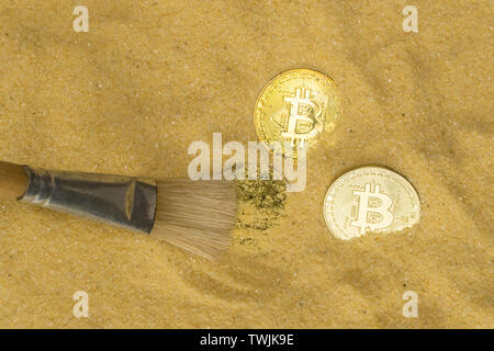 an archaeologist with a brush clears the bitcoin coin on the golden sand. top view. finding and mining cryptocurrency - Stock Image