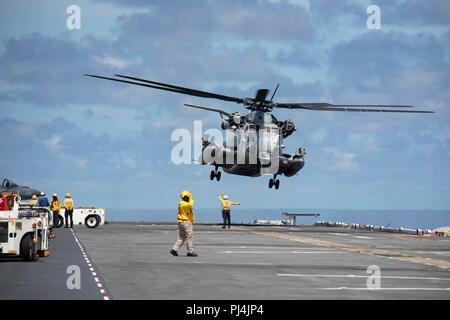 180827-N-KW492-0095 ATLANTIC OCEAN (Aug. 27, 2018) A CH-53E Super Stallion takes off from the flight deck of the Wasp-class amphibious assault ship USS Kearsarge (LHD3) during the Carrier Strike Group FOUR (CSG 4) Amphibious Ready Group, Marine Expeditionary Unit Exercise (ARGMEUEX). Kearsarge Amphibious Ready Group and 22nd Marine Expeditionary Unit are enhancing joint integration, lethality and collective capabilities of the Navy-Marine Corps team through joint planning and execution of challenging and realistic training scenarios. CSG 4 mentors, trains and assesses East Coast units preparin - Stock Image