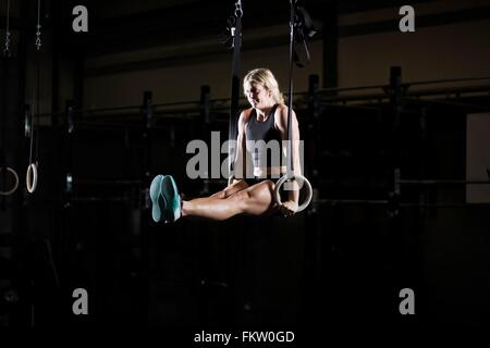 Young woman poised on gym rings in dark gym - Stock Image