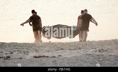 A team of U.S. Army Soldiers carry a Zodiac rigid inflatable boat during one of the events of the 74th Engineer Dive Detachment's Diver Fitness Challenge at Kuwait Naval Base, Kuwait, Aug. 31, 2018. The events of the Diver Fitness Challenge are not exercises typically done by Soldiers in the U.S. Army, so they provide a unique opportunity for Soldiers to increase their capabilities by trying new challenges. (U.S. Army photo by Spc. Adam Parent) - Stock Image