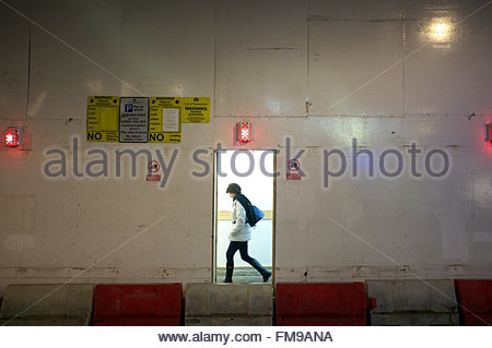 Pedestrian walking past a construction site at night, with building site safety panelling providing protection. - Stock Image