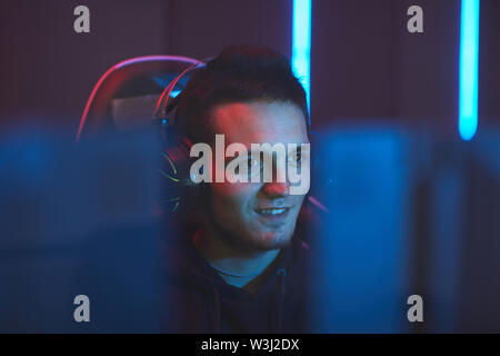 Smiling excited handsome young gamer in headset sitting in dark room and watching computer monitor - Stock Image