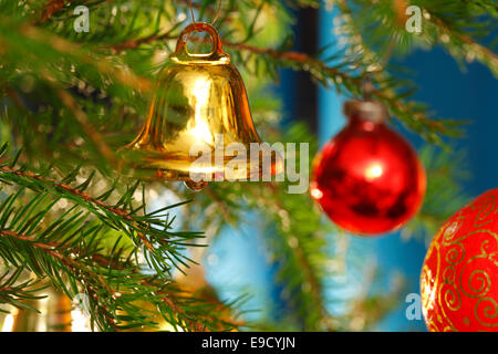 A golden  bell is hanging together with red baubles on the Christmas tree. - Stock Image