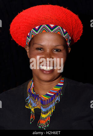Shakaland Zulu girl in  a traditional Zulu hat  poses for the camera  at the Shakaland Cultural Village, - Stock Image