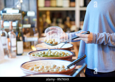 Close Up Of Female Customer In Delicatessen Filling Pot With Green Olives - Stock Image