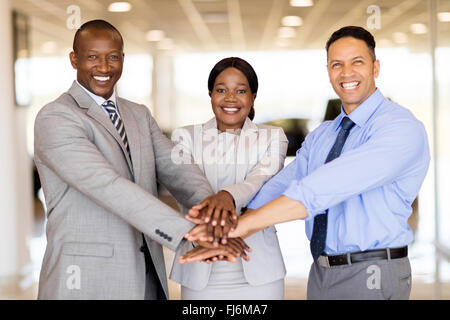 happy vehicle sales team putting their hands together inside showroom - Stock Image