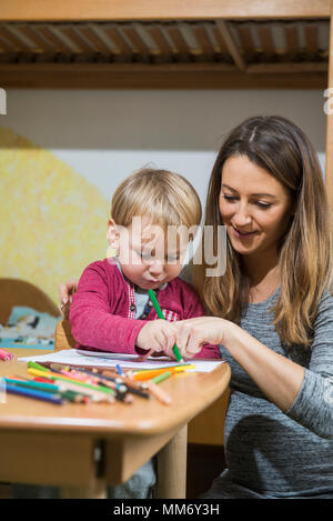 Mother assisting son to draw with colored pencil, Munich, Germany - Stock Image