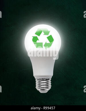 Illuminated energy efficient Light Emitting Diode LED light bulb with recycling symbol inside. Concept of ecology, environmental conservation; green a - Stock Image