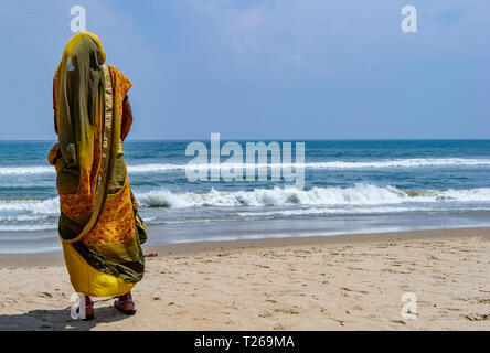 An old lady with a walking stick enjoys the the tranquility and peace of the sea at Marina Beach, with the Bay of Bengal in Chennai, India - Stock Image