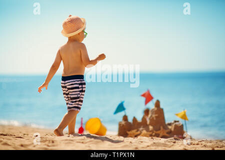 boy sitting smiling at the beach - Stock Image