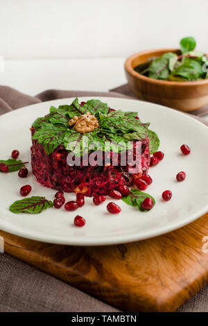 Beet salad with pomegranate, walnuts, prunes and spinach. Cafe menu on a wooden background in warm colors with copy space. - Stock Image