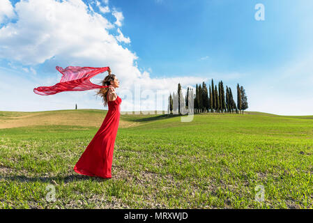San Quirico d'Orcia, Orcia valley, Siena, Tuscany, Italy. A young woman in red dress relaxing in a wheat field near the cypresses of Orcia valley - Stock Image