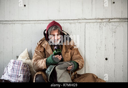 A front view of homeless beggar man sitting outdoors in city asking for money donation, holding a bottle of alcohol. Copy space. - Stock Image