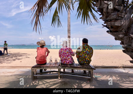 Man and two female companions sitting on a bench and overlooking the ocean at Pattaya beach, Thailand, Southeast Asia - Stock Image