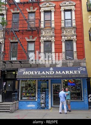 Two men outside Holyland Market, 122 St Marks Place, East Village, New York, NYC, NY, USA - Stock Image