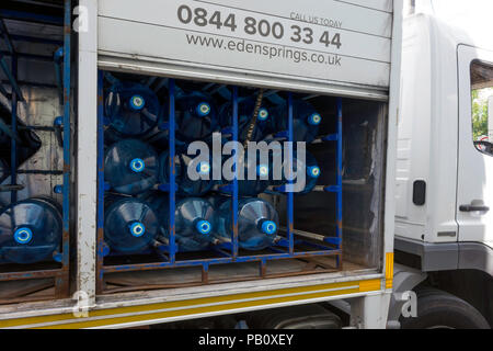 A lorry delivering large bottles of drinking water for use in commercial premises with side doors open - Stock Image