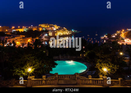 View of St. George's Bay seafront lights by night, with a blue luxury swimming pool and boats and yachts anchored. St Julian's or San Giljan, Central  - Stock Image