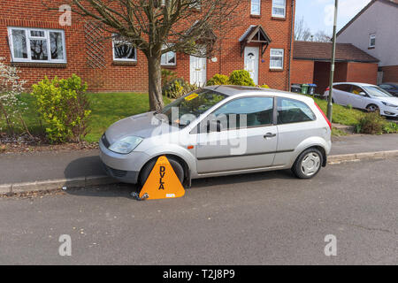 Untaxed car immobilised at the roadside by a yellow DVLA wheelclamp with sticker on the windscreen of non-payment of road tax - Stock Image