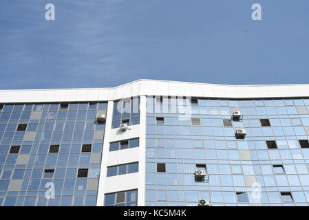 Glass panels in white and blue of a modern high rise building exterior with reflective windows and summer sky - Stock Image