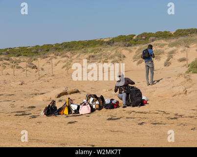 Black beach salesmen preparing his goods ready for a day of selling at Guardamar del Segura, Costa Blanca, Spain - Stock Image