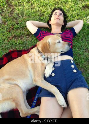 Woman and her Labrador retriever lying on her on a picnic rug in a park - Stock Image