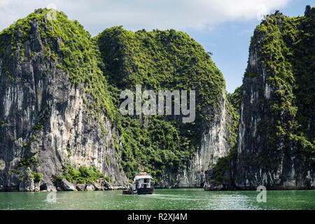 A Tourists boat sails between steep sided limestone rock islands in Halong Bay in South China Sea. Ha Long, Quảng Ninh, Vietnam, Asia - Stock Image