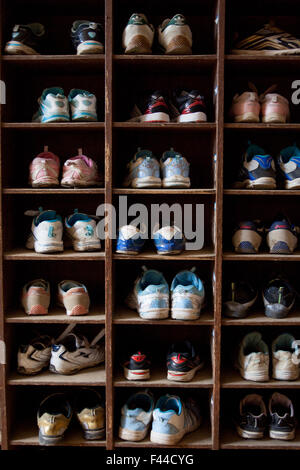 Cubbyhole containing childrens shoes - Stock Image