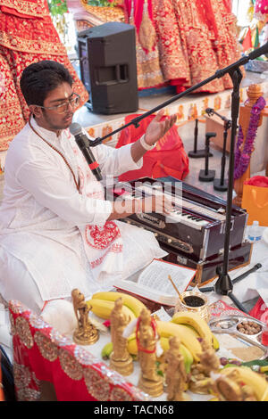 A teenage prodigy priest singing a prayer and playing the harmonium at a Hindu temple in Jamaica, Queens, New York City, - Stock Image