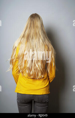 rear view of young woman with long blond hair standing facing wall - Stock Image