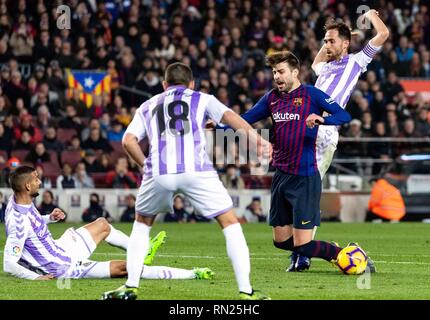 Barcelona, Spain. 16th Feb, 2019. Barcelona's Gerard Pique (2nd R) is fouled by Valladolid's Michel Herrero (1st R) in penalty area during a Spanish league match between FC Barcelona and Valladolid in Barcelona, Spain, on Feb. 16, 2019. FC Barcelona won 1-0. Credit: Joan Gosa/Xinhua/Alamy Live News - Stock Image