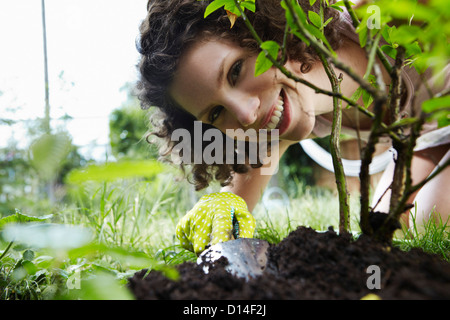 portrait of young woman planting a plant in the garden - Stock Image