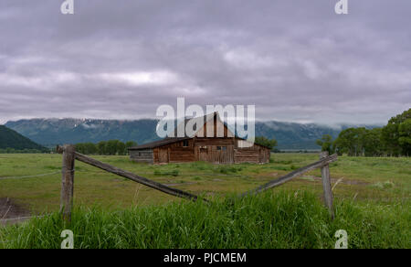 Barn Framed by Fence in front of mountains and fog - Stock Image