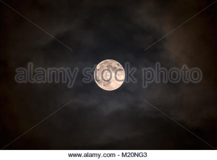 Super moon Blue moon against clouds in sky - Stock Image