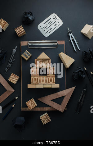 House construction, planning, and repairment concept. Wooden block home on a clipboard with engineering equipment, compasses, rulers and pencils. - Stock Image