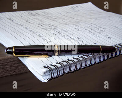 Classic Montblanc fountain pen resting on a pad of paper with handwriting - Stock Image