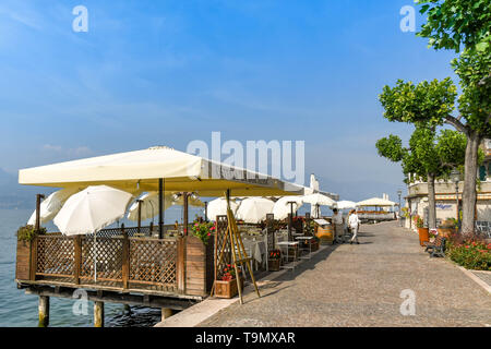 TORRI DEL BENACO, LAKE GARDA, ITALY - SEPTEMBER 2018: Outdoor dining area with sun canopy at a restaurant on the promenade on the edge of Lake Garda - Stock Image