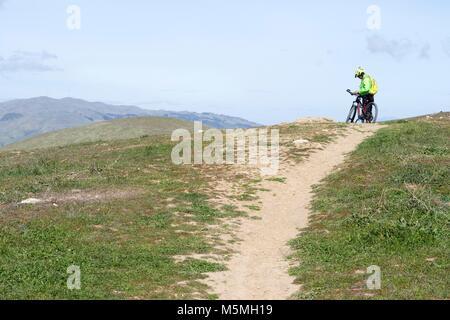 A man takes a break from mountain biking at Sierra Vista in San Jose. - Stock Image