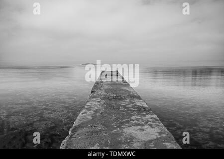Wooden jetty on sea and sky reflection on the water. Long exposure and black & white photo - Stock Image